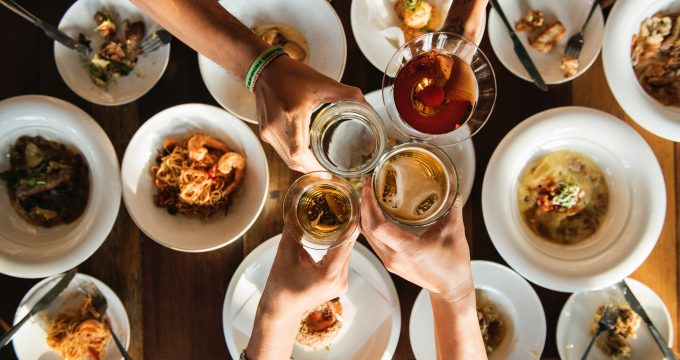 glasses raised in a toast above many small plates of food